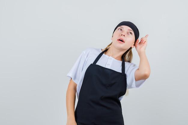 Jeune serveuse en uniforme et tablier s'inclinant la tête et pointant vers le haut