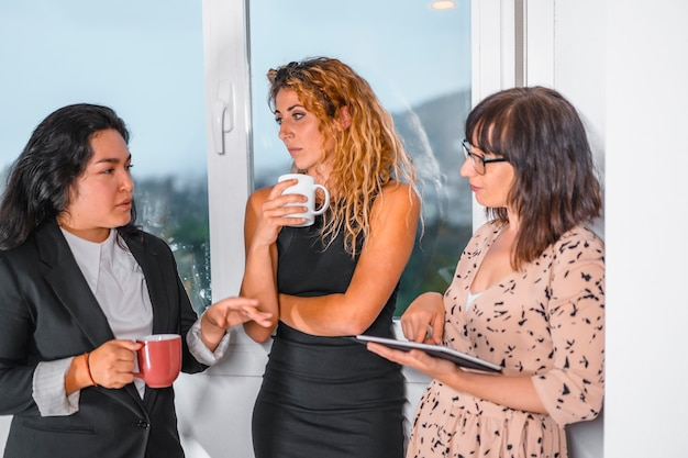 Jeune session entrepreneuriale au bureau, deux jeunes filles de race blanche et une jeune latina au bureau pendant la pause en prenant un thé