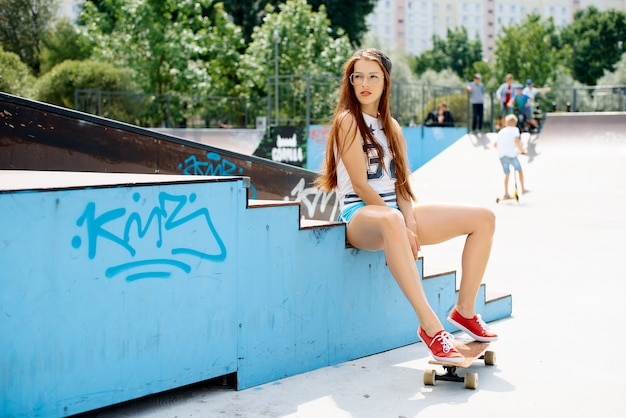 Jeune sexy belle fille mince se repose avec une planche à roulettes dans la ville. hipster fille à la mode dans une casquette et des lunettes de soleil.
