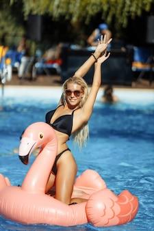 Jeune et sexy fille s'amusant et riant s'amusant dans la piscine sur un flamant rose gonflable en