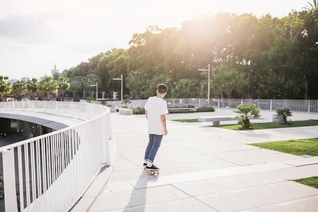 Jeune skateur à bord d'équitation dans le parc