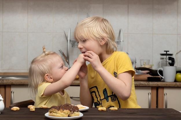 Une jeune soeur blonde traite son frère avec des bonbons