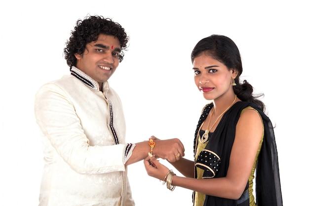 Jeune soeur indienne attachant rakhi au poignet de son frère, une tradition à l'occasion du festival raksha bandhan