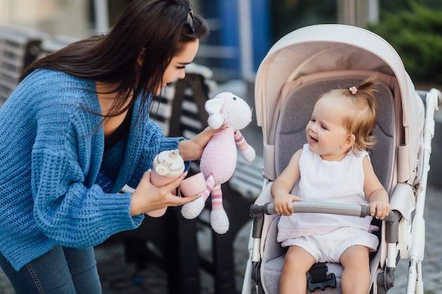 Jeune soeur marchant avec sa petite soeur mignonne à l'extérieur lui donne de l'eau