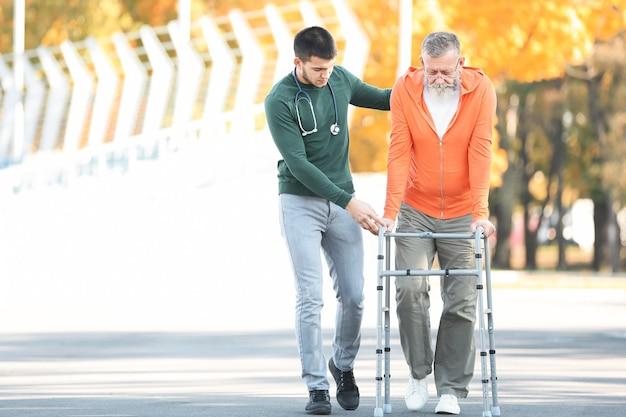 Jeune soignant marchant avec un homme âgé, à l'extérieur