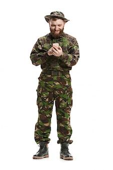 Jeune soldat de l'armée portant l'uniforme de camouflage isolé sur blanc
