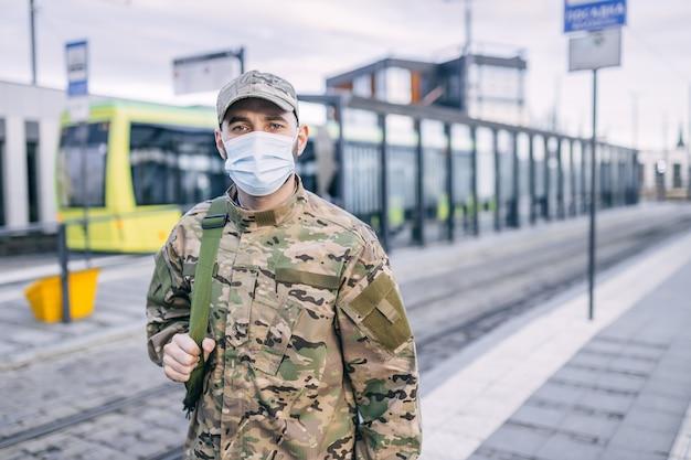 Un jeune soldat en tenue de camouflage et un masque de protection dans la rue