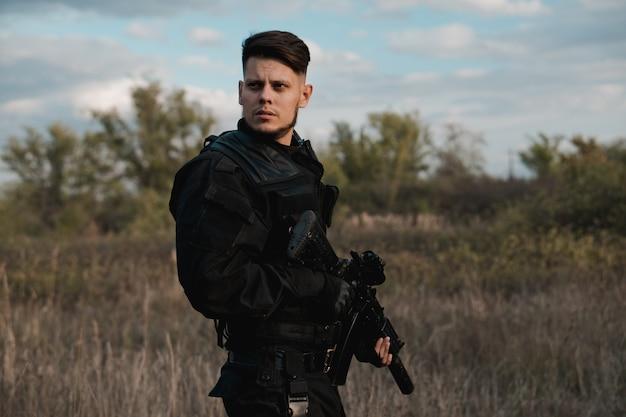 Jeune soldat en uniforme noir avec un fusil d'assaut