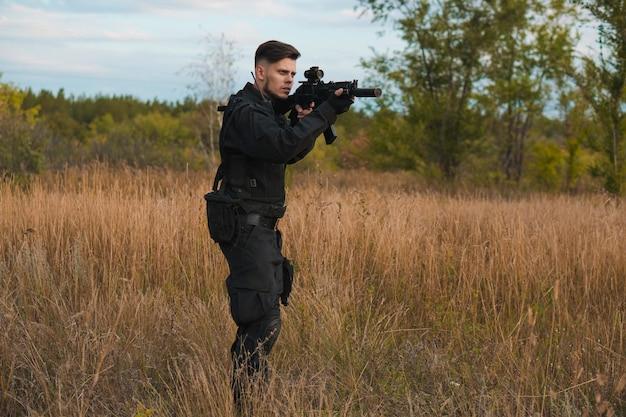 Jeune soldat en uniforme noir visant un fusil d'assaut