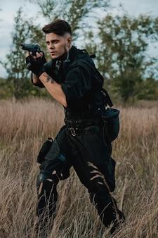 Jeune soldat en uniforme noir visant un pistolet