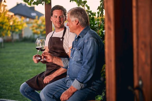 Jeune sommelier confiant souriant à un homme mûr assis dehors avec lui. verres de vin rouge dans leurs mains