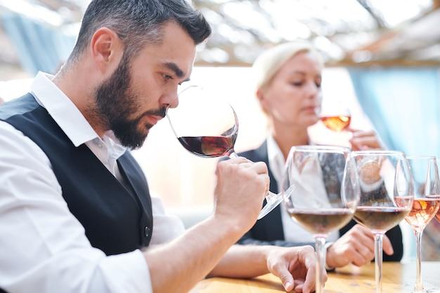 Jeune sommelier sérieux sentant l'odeur du vin rouge tout en tenant le verre à vin par son nez pendant le travail en cave