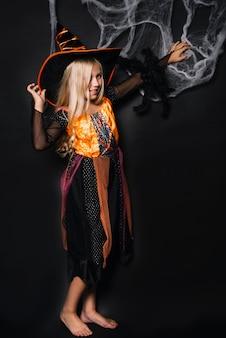 Jeune sorcière blonde avec une araignée touchant le web