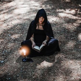 Jeune sorcière avec livre et chandelier brûlant sur un terrain forestier