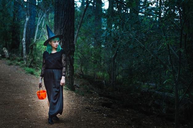 Jeune sorcière avec panier debout dans la forêt