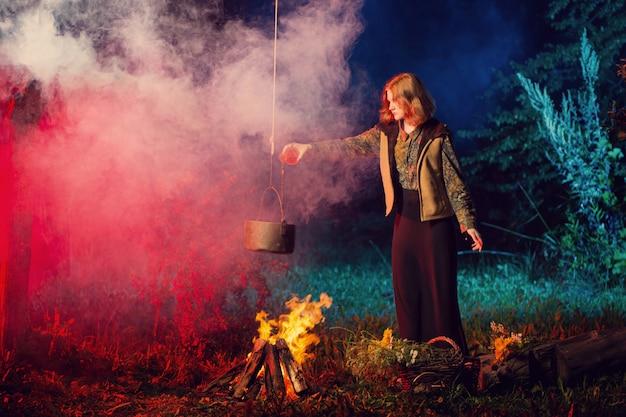 Jeune sorcière par le feu dans la forêt de nuit prépare une potion magique