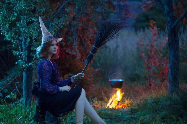 Jeune sorcière par le feu dans la forêt de nuit