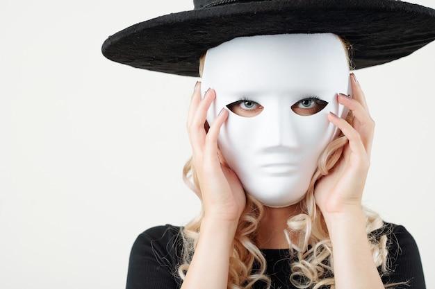Jeune sorcière se cachant derrière un masque