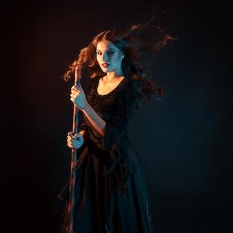 La jeune sorcière se précipite vers le sabbat jeune belle brune dans une robe de sorcière