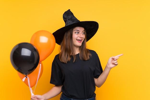 Jeune sorcière tenant des ballons à air noir et orange pour les fêtes d'halloween surpris et pointant le côté