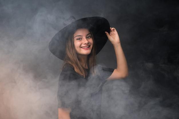 Jeune sorcière tenant des ballons à air noir et orange pour des fêtes d'halloween