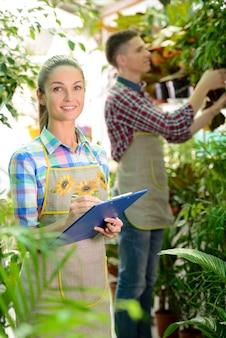 Jeune souriant fleuristes homme et femme travaillant en serre.