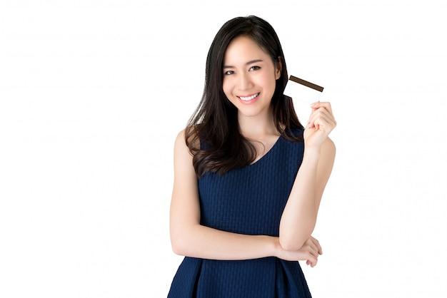 Jeune souriante belle femme asiatique présentant la carte de crédit en main