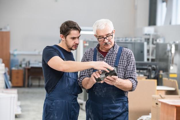 Jeune spécialiste en montrant à un collègue senior comment utiliser le contrôleur en usine