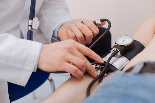 Jeune spécialiste qualifié et précis s'assurant que la pression du patient ne dépasse pas la limite pendant qu'il est allongé sur le lit et ne bouge pas
