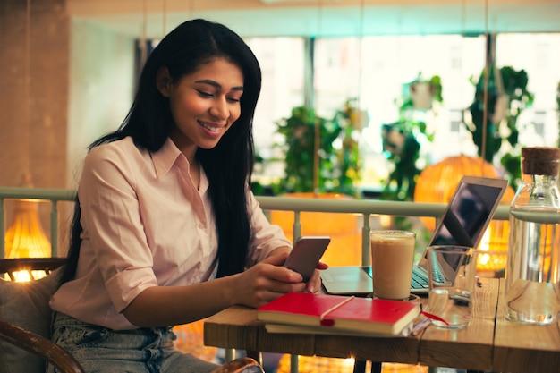 Jeune spécialiste travaillant à la table du café avec un ordinateur portable dessus et souriant en regardant l'écran de son smartphone
