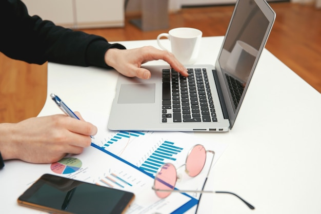 Un jeune spécialiste travaille avec des documents financiers sur un ordinateur.