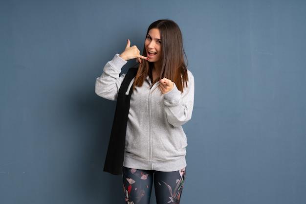 Jeune sport femme faisant un geste de téléphone et pointant devant