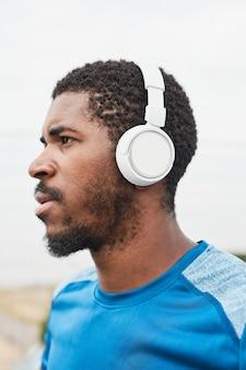 Jeune sportif africain dans des écouteurs sans fil écoutant de la musique à l'extérieur