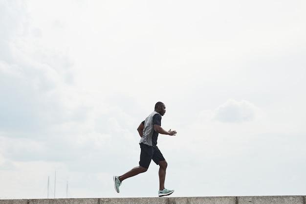 Jeune sportif africain faisant du jogging le matin à l'extérieur contre le ciel bleu