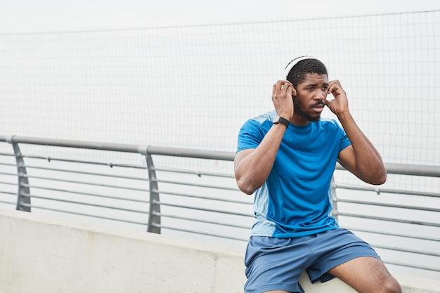 Jeune sportif africain mettant des écouteurs écoutant de la musique et se reposant après s'être entraîné à l'extérieur