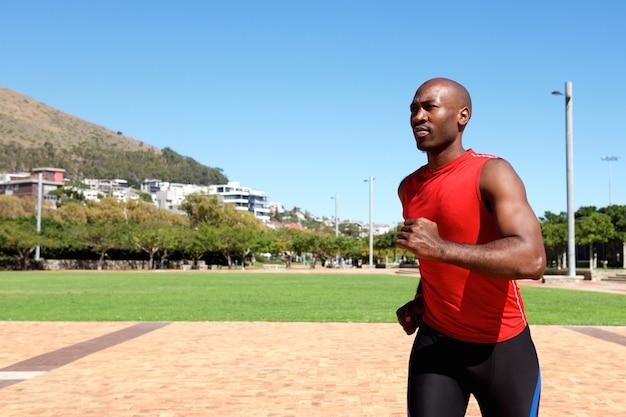 Jeune sportif africain qui court à l'extérieur du parc