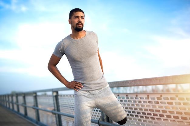 Jeune sportif afro-américain attrayant, échauffement des jambes avant de courir entraînement fitness et mode de vie actif.