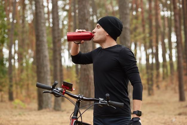 Jeune sportif athlétique assoiffé d'eau potable avec les yeux fermés, ayant une expression faciale paisible, debout de profil, tenant son vélo, étant en forêt pendant l'entraînement. concept sportif.