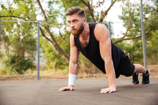 Jeune sportif barbu séduisant faisant des pompes à l'extérieur