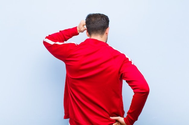 Jeune sportif bel ou moniteur se sentir désemparé et confus, pensant une solution, avec la main sur la hanche et autre sur la tête, vue arrière contre le mur plat