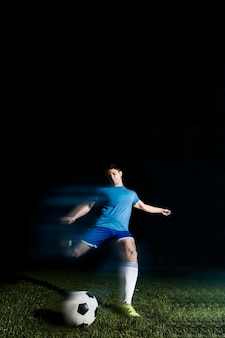 Jeune sportif botter le ballon de soccer