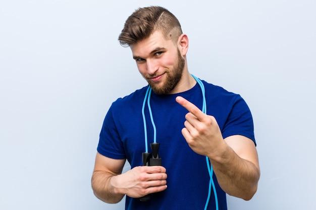 Jeune sportif caucasien avec une corde à sauter pointant avec le doigt sur vous comme si vous invitiez à vous rapprocher.