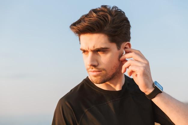 Jeune sportif ciblé en t-shirt noir dans les écouteurs