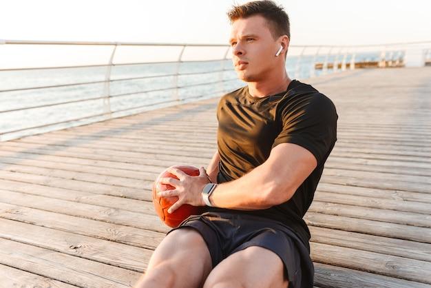 Jeune sportif concentré dans des écouteurs faisant des exercices
