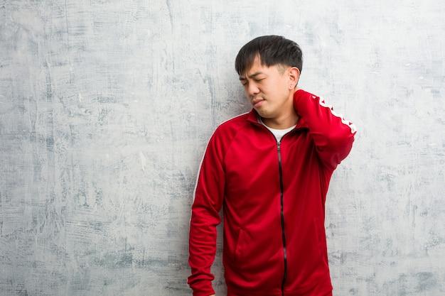 Jeune sportif fitness chinois souffrant de douleurs au cou