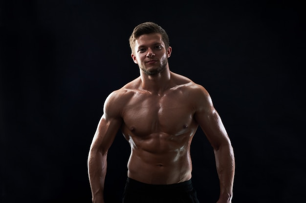 Jeune sportif en forme musculaire posant torse nu sur backgroun noir