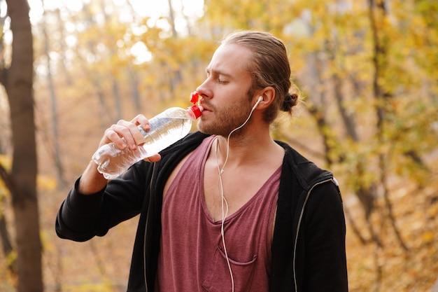 Jeune sportif en forme séduisant faisant du jogging dans la forêt d'automne, écoutant de la musique avec des écouteurs, tenant une bouteille d'eau