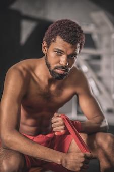 Jeune sportif. jeune sportif à la peau foncée dans une salle de sport se préparant pour l'entraînement