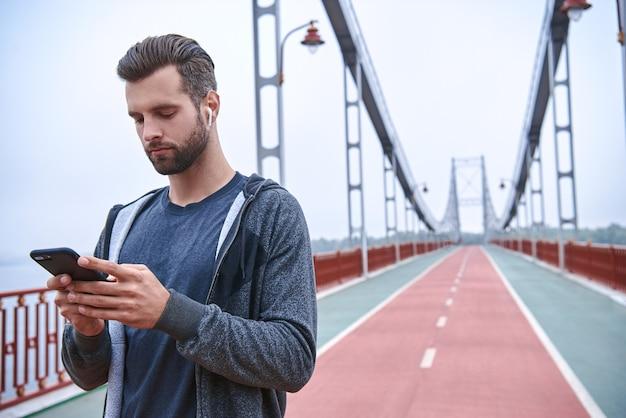 Jeune sportif sérieux utilisant un tracker de fitness et un smartphone à l'extérieur