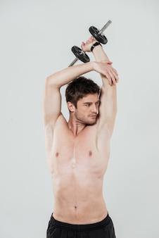 Jeune sportif torse nu, faire des exercices avec un haltère